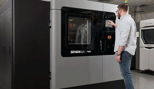 a man working with a Stratasys F900 printer